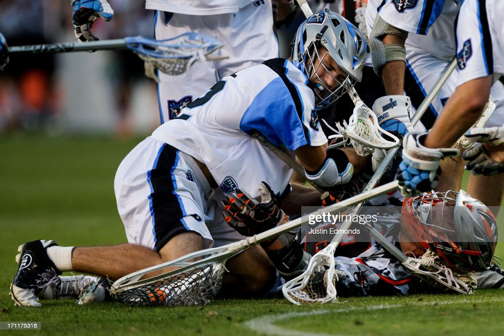 Brendan Mundorf #2 of the Denver Outlaws gets checked by Ray Megill #12 of the Ohio Machine while battling for a ground ball during the third quarter at Sports Authority Field at Mile High on June 22, 2013 in Denver, Colorado. The Outlaws defeated the Machine 19-5 to improve to 8-0 on the season.