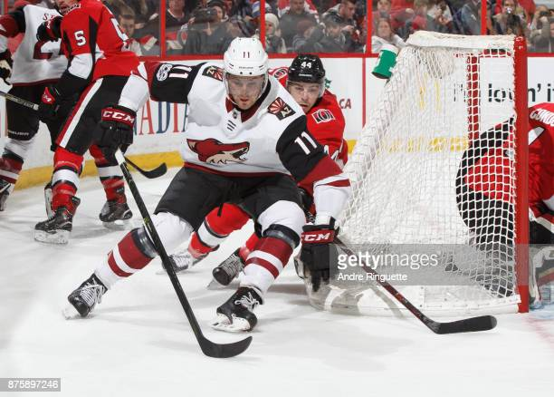 Brendan Perlini of the Arizona Coyotes controls the puck behind the net as JeanGabriel Pageau of the Ottawa Senators pressures on the backcheck at...