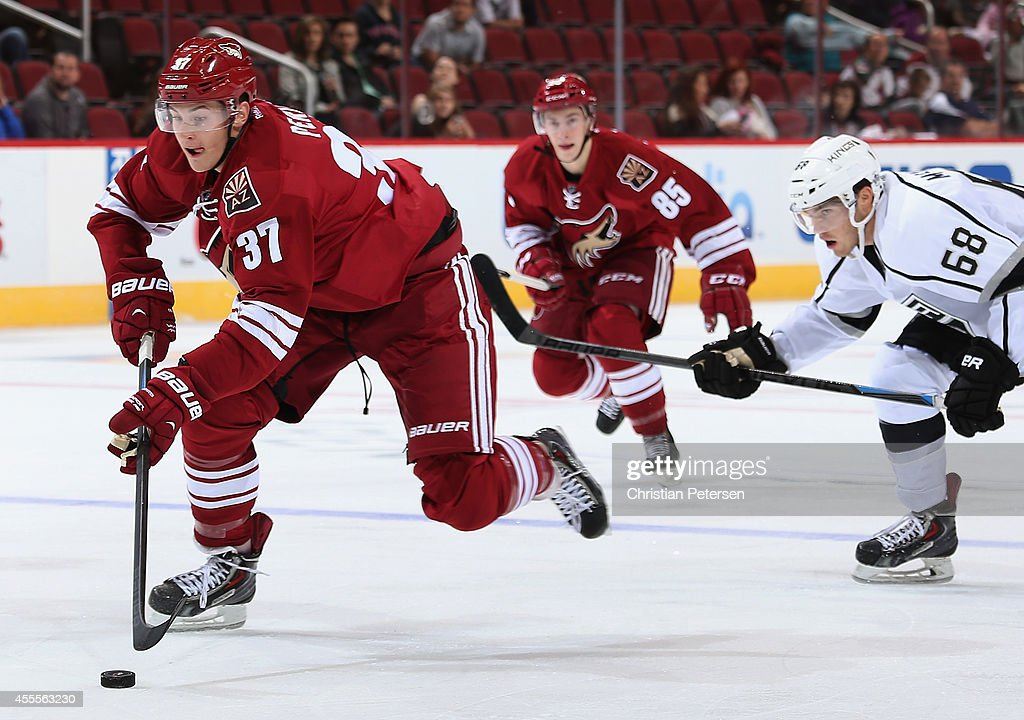 Brendan Perlini #37 of the Arizona Coyotes skates with the puck ahead of Roland McKeown #68 of the Los Angeles Kings during the NHL rookie camp game at Gila River Arena on September 16, 2014 in Glendale, Arizona.