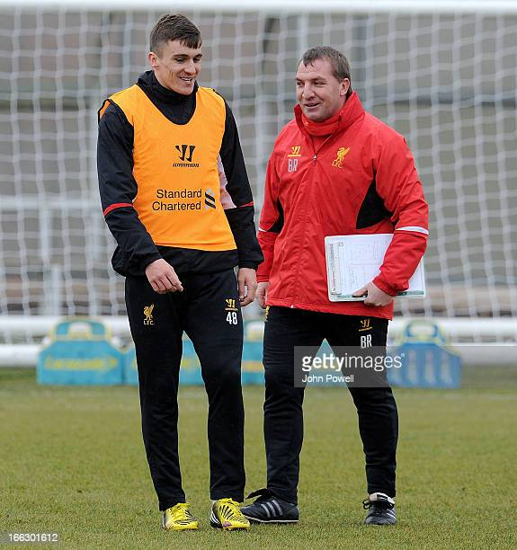 Brendan Rodgers manager of Liverpool talks with Adam Morgan during a training session at Melwood Training Ground on April 11 2013 in Liverpool England