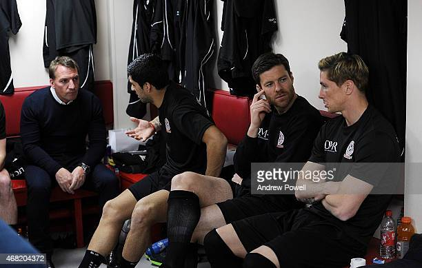 Brendan Rodgers talking with Luis Suarez and Xabi Alsonso talking with Fernando Torres in the dressing room before the Liverpool All Star Charity...