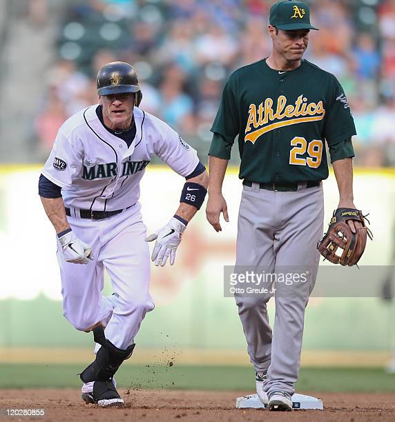 Brendan Ryan of the Seattle Mariners advances to third base after singling and taking second as third baseman Scott Sizemore of the Oakland Athletics...