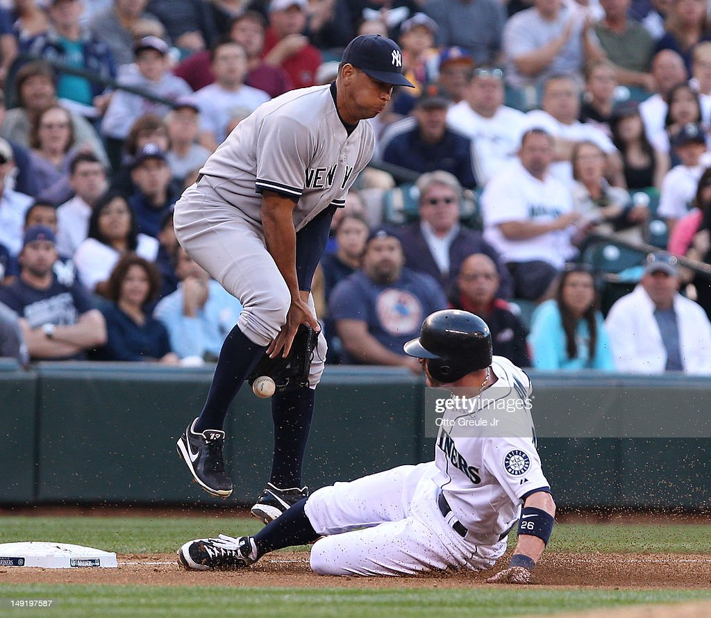 Brendan Ryan #26 of the Seattle Mariners advances to third from first on a single by Michael Saunders against Alex Rodriguez #13 of the New York Yankees at Safeco Field on July 24, 2012 in Seattle, Washington.