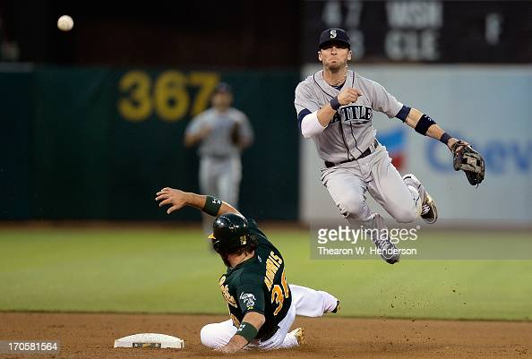 Brendan Ryan of the Seattle Mariners gets his throw off but not in time to complete the doubleplay while avoiding the slide of Derek Norris of the...