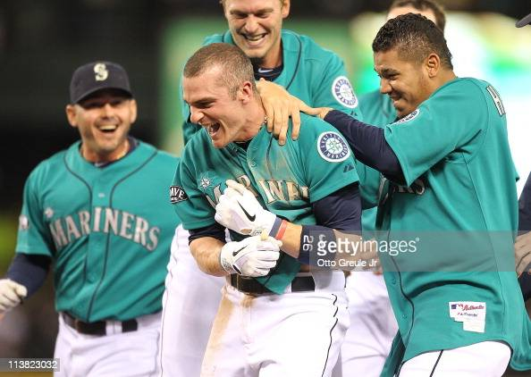 Brendan Ryan of the Seattle Mariners is mobbed by teammates including starting pitcher Felix Hernandez after driving in the winning run in the ninth...