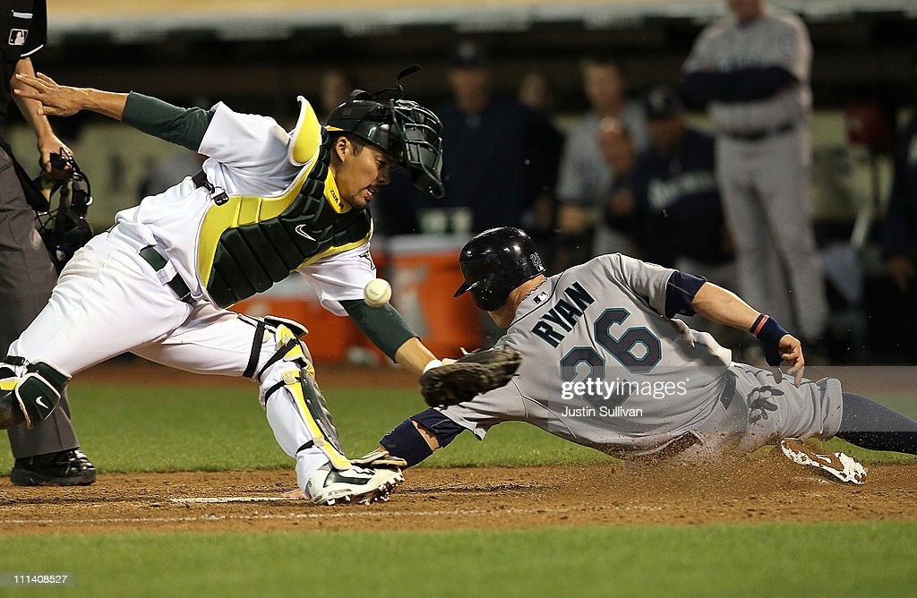 Brendan Ryan of the Seattle Mariners slides into home safely past Kurt Suzuki of the Oakland Athletics during the sixth inning at the OaklandAlameda...
