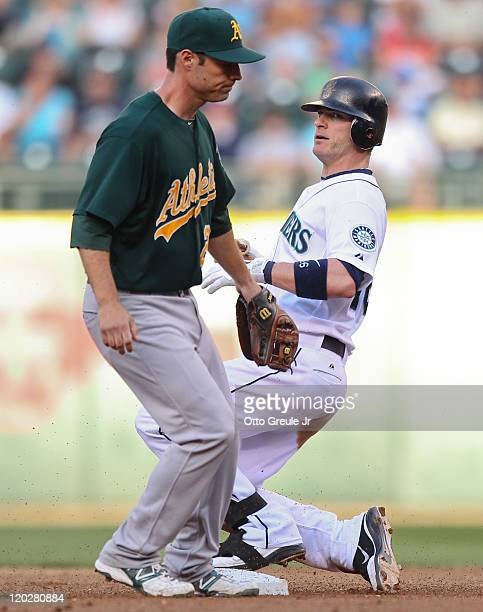 Brendan Ryan of the Seattle Mariners takes second base after singling as third baseman Scott Sizemore of the Oakland Athletics arrives late to cover...