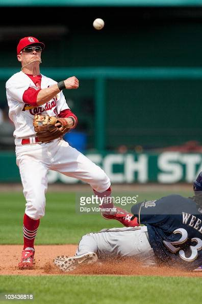 Brendan Ryan of the St Louis Cardinals turns a double play over Rickie Weeks of the Milwaukee Brewers at Busch Stadium on August 18 2010 in St Louis...