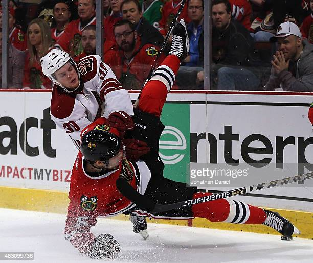 Brendan Shinnimin of the Arizona Coyotes dumps David Rundblad of the Chicago Blackhawks at the United Center on February 9 2015 in Chicago Illinois