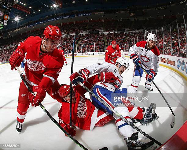 Brendan Smith and Joakim Andersson of the Detroit Red Wings battle for the puck in the corner with Lars Eller and Brandon Prust of the Montreal...