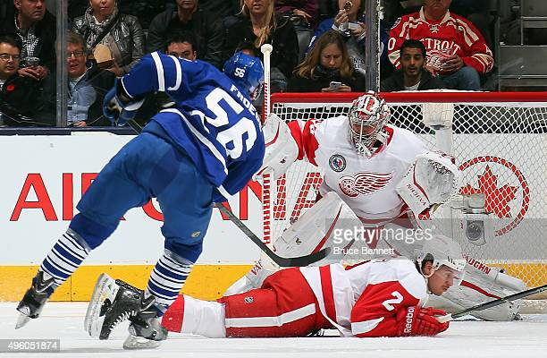 Brendan Smith and Petr Mrazek of the Detroit Red Wings defend the net against Byron Froese of the Toronto Maple Leafs during the second period at the...