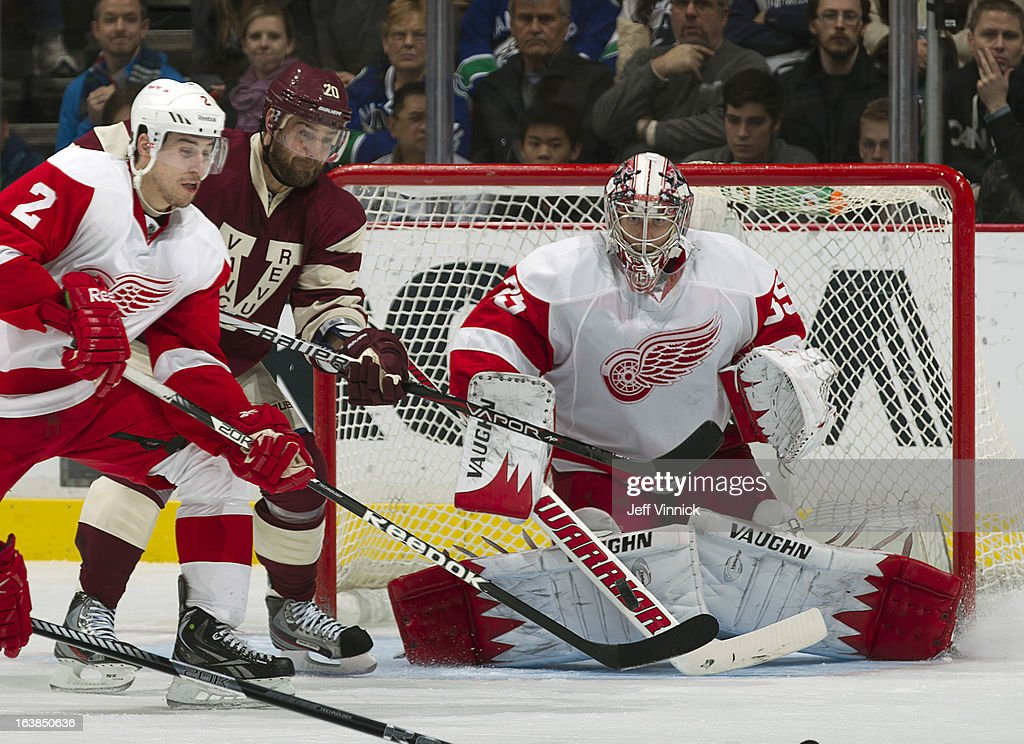 Brendan Smith #2 of the Detroit Red Wings and Chris Higgins #20 of the Vancouver Canucks get their sticks in the line of Jimmy Howard #35 of the Red Wings during their NHL game at Rogers Arena March 16, 2013 in Vancouver, British Columbia, Canada. Detroit won 5-2.