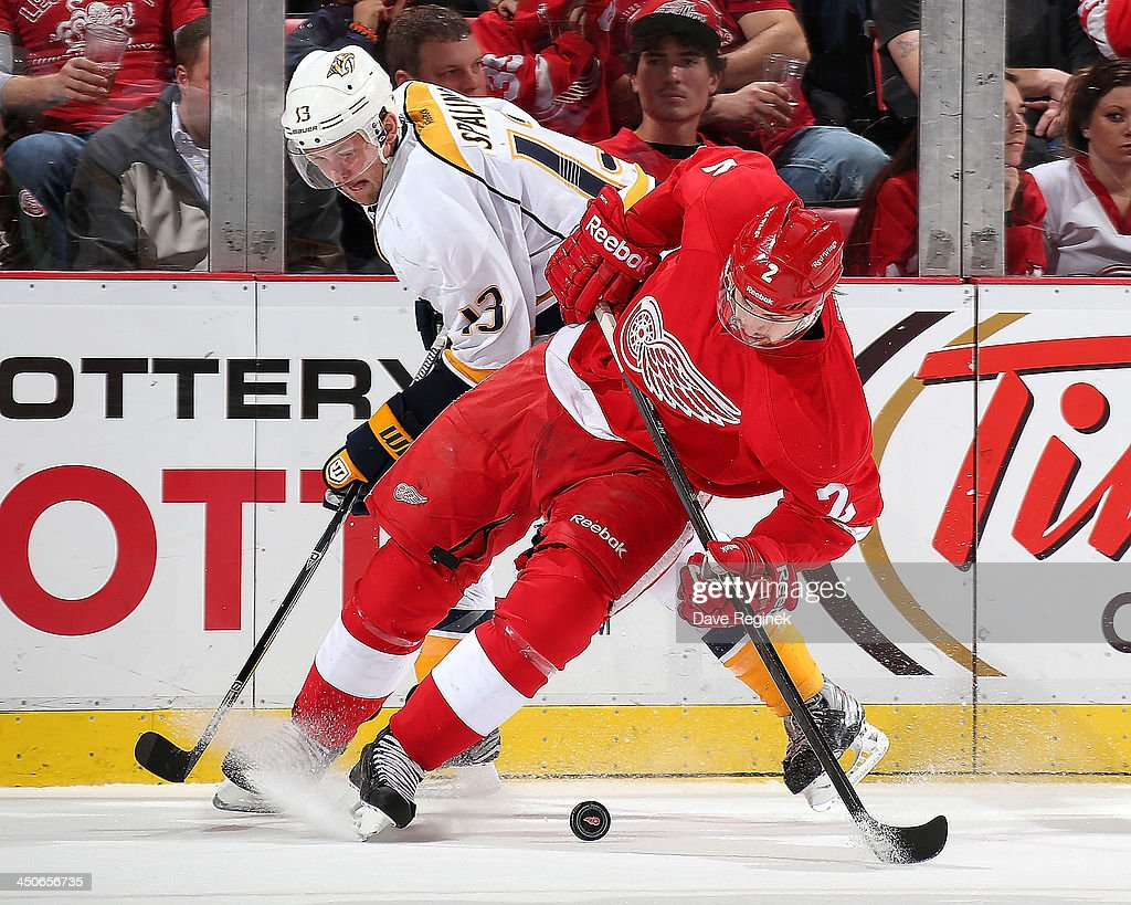 Brendan Smith #2 of the Detroit Red Wings and <a gi-track='captionPersonalityLinkClicked' href=/galleries/search?phrase=Nick+Spaling&family=editorial&specificpeople=4112920 ng-click='$event.stopPropagation()'>Nick Spaling</a> #13 of the Nashville Predators battle for the puck during an NHL game at Joe Louis Arena on November 19, 2013 in Detroit, Michigan. Nashville defeated Detroit 2-0