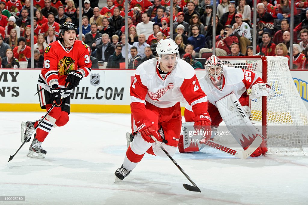 Brendan Smith #2 of the Detroit Red Wings lunges for the puck, as Dave Bolland #36 of the Chicago Blackhawks yells out from behind and goalie Jimmy Howard #35 of Detroit guards the net, during the NHL game on January 27, 2013 at the United Center in Chicago, Illinois.