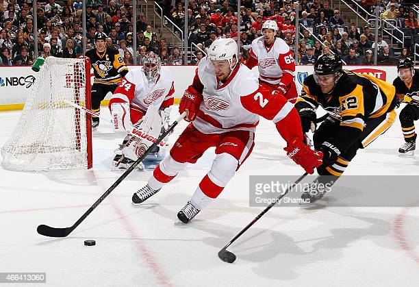Brendan Smith of the Detroit Red Wings moves the puck in front of Ben Lovejoy of the Pittsburgh Penguins at Consol Energy Center on March 15 2015 in...