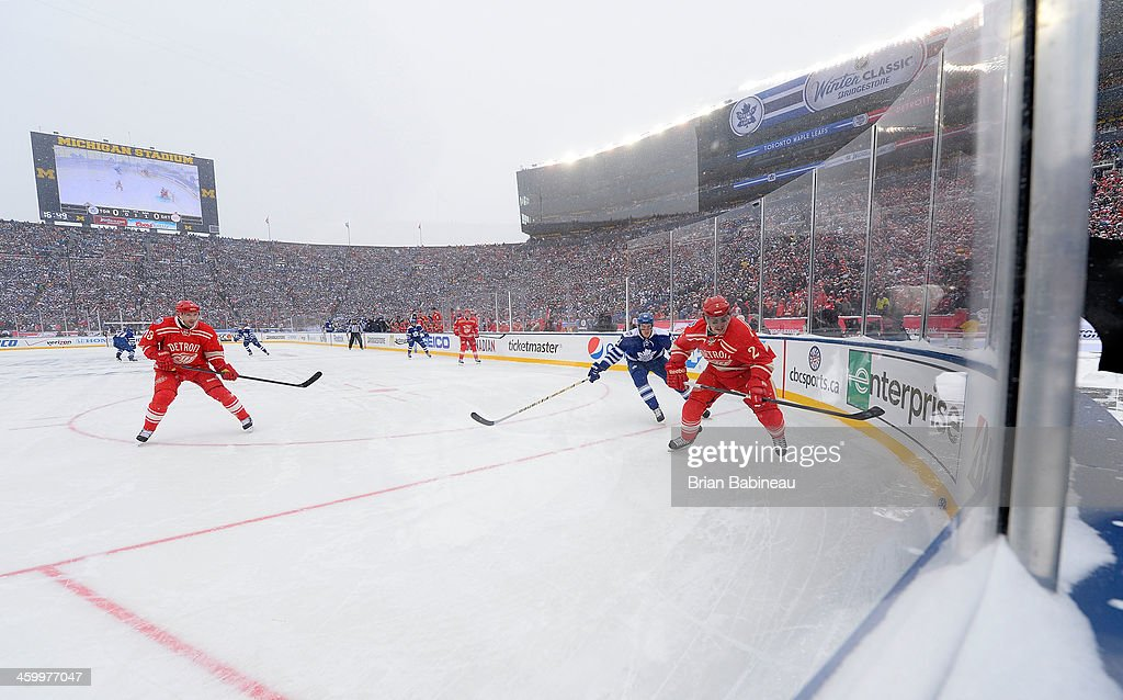 Brendan Smith #2 of the Detroit Red Wings skates after the puck while under pressure from James van Riemsdyk #21 of the Toronto Maple Leafs as <a gi-track='captionPersonalityLinkClicked' href=/galleries/search?phrase=Pavel+Datsyuk&family=editorial&specificpeople=202893 ng-click='$event.stopPropagation()'>Pavel Datsyuk</a> #13 of the Detroit Red Wings gives support to Smith in the first period during the 2014 Bridgestone NHL Winter Classic on January 1, 2014 at Michigan Stadium in Ann Arbor, Michigan.