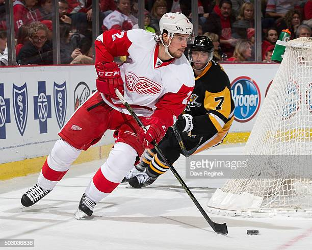 Brendan Smith of the Detroit Red Wings skates around the net with the puck in front of Matt Cullen of the Pittsburgh Penguins during an NHL game at...