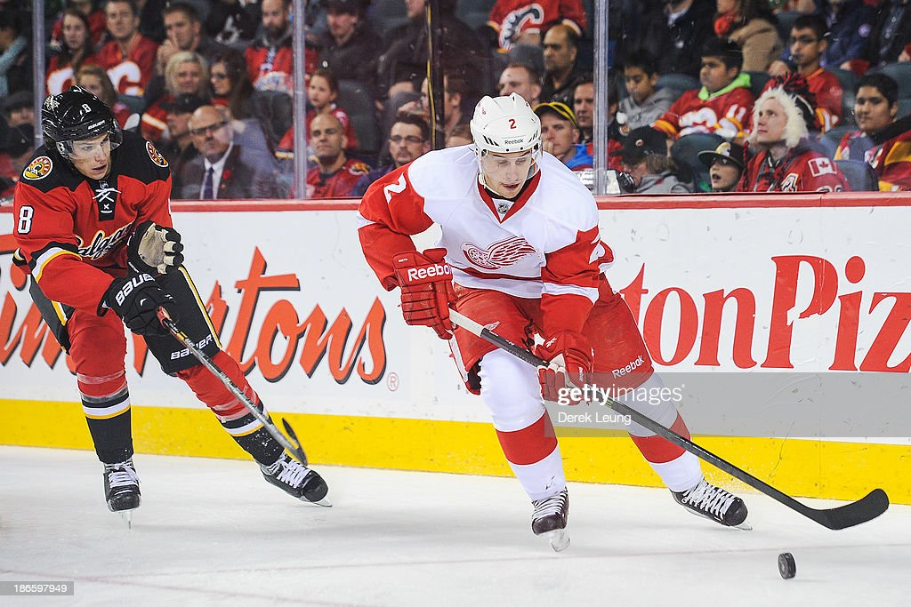 Brendan Smith #2 of the Detroit Red Wings skates with the puck past the defense of <a gi-track='captionPersonalityLinkClicked' href=/galleries/search?phrase=Joe+Colborne&family=editorial&specificpeople=5370968 ng-click='$event.stopPropagation()'>Joe Colborne</a> #8 of the Calgary Flames during an NHL game at Scotiabank Saddledome on November 1, 2013 in Calgary, Alberta, Canada. The Red Wings defeated the Flames 4-3.