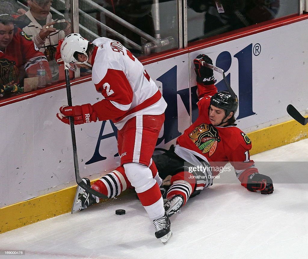 Brendan Smith #2 of the Detroit Red Wings tries to clear the puck from between the legs of <a gi-track='captionPersonalityLinkClicked' href=/galleries/search?phrase=Daniel+Carcillo&family=editorial&specificpeople=2116181 ng-click='$event.stopPropagation()'>Daniel Carcillo</a> #13 of the Chicago Blackhawks in Game Two of the Western Conference Semifinals during the 2013 NHL Stanley Cup Playoffs at the United Center on May 18, 2013 in Chicago, Illinois.