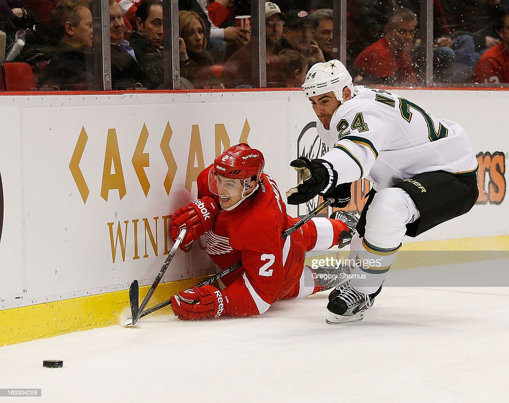 Brendan Smith #2 of the Detroit Red Wings tries to control the puck while falling to the ice in front of Eric Nystrom #24 of the Dallas Stars during the first period at Joe Louis Arena on January 22, 2013 in Detroit, Michigan.