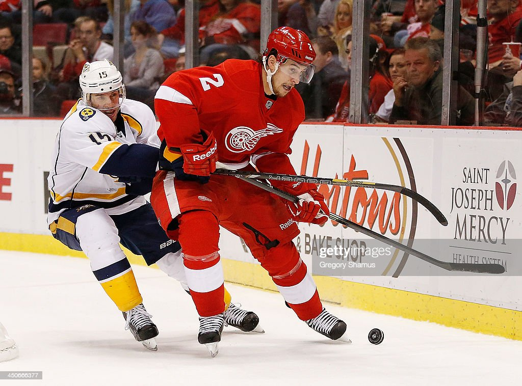 Brendan Smith #2 of the Detroit Red Wings tries to get control of the puck in front of Craig Smith #15 of the Nashville Predators during the third period at Joe Louis Arena on November 19, 2013 in Detroit, Michigan. Nashville won the game 2-0.