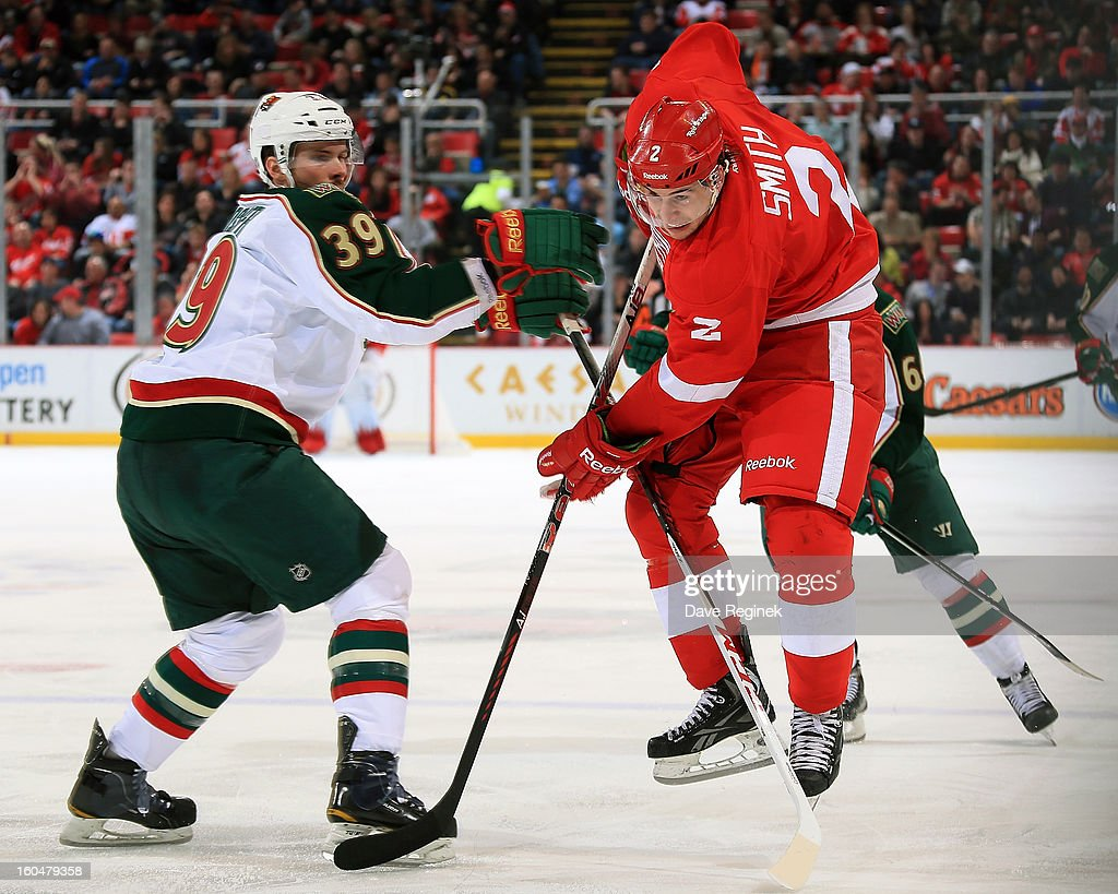 Brendan Smith #2 of the Detroit Red Wings tries to skate past the defense of Nate Prosser #39 of the Minnesota Wild during a NHL game at Joe Louis Arena on January 25, 2013 in Detroit, Michigan. Detroit won the game 5-3