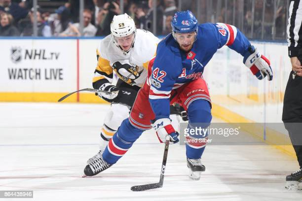 Brendan Smith of the New York Rangers skates against Jake Guentzel of the Pittsburgh Penguins at Madison Square Garden on October 17 2017 in New York...