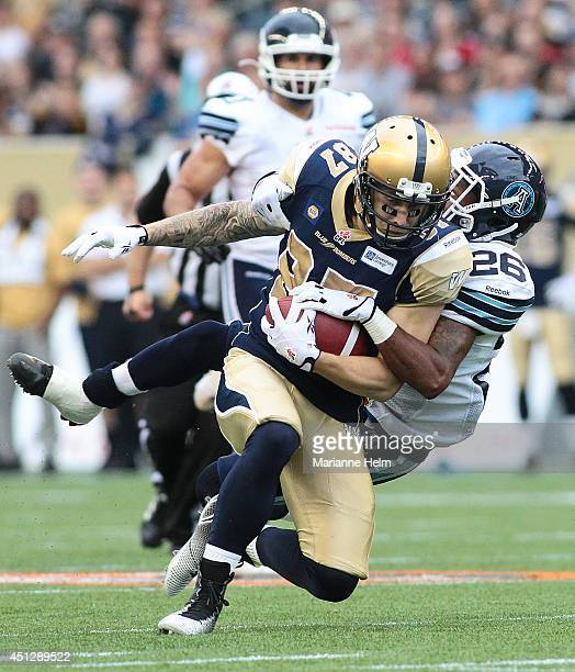 Brendan Smith of the Toronto Argonauts takes down Rory Kohlert of the Winnipeg Blue Bombers in first half action in a CFL game at Investors Group...