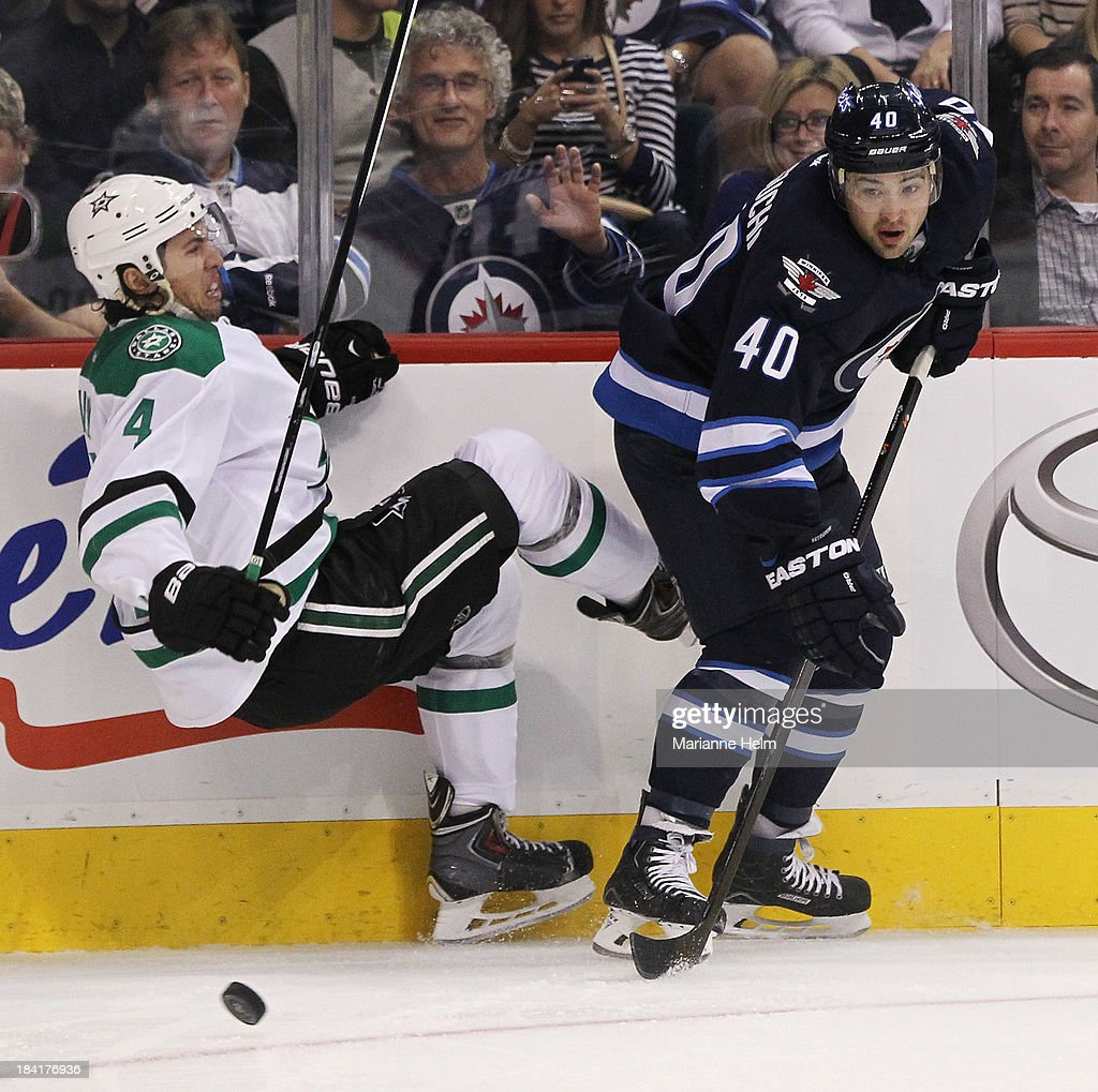 Brenden Dillon #4 of the Dallas Stars and Devin Setoguchi #40 of the Winnipeg Jets collide along the boards in second-period action of an NHL game at the MTS Centre on October 11, 2013 in Winnipeg, Manitoba, Canada.