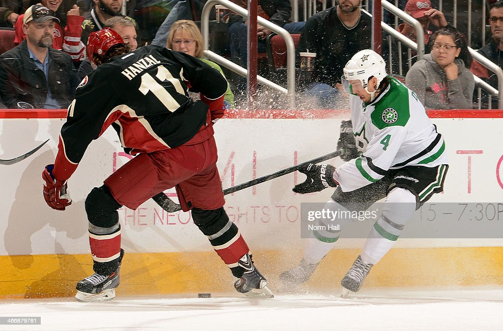 Brenden Dillon #4 of the Dallas Stars and Martin Hanzal #11 of the Phoenix Coyotes chase down a loose puck during the third period at Jobing.com Arena on February 4, 2014 in Glendale, Arizona.