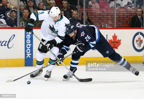 Brenden Dillon of the San Jose Sharks and Blake Wheeler of the Winnipeg Jets battle for the loose puck during second period action at the MTS Centre...