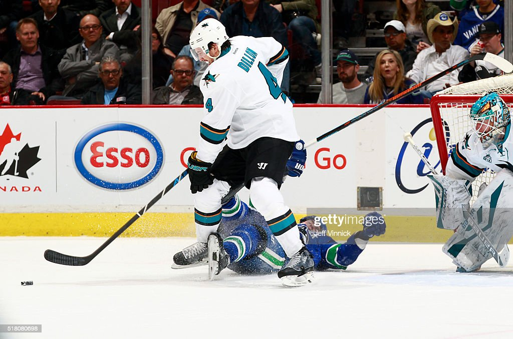 Brenden Dillon #4 of the San Jose Sharks plays the puck after Alexandre Burrows #14 of the Vancouver Canucks clipped the goal and tripped during their NHL game at Rogers Arena March 29, 2016 in Vancouver, British Columbia, Canada. San Jose won 4-1.