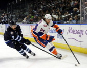 Brenden Kichton of the St John's IceCaps reaches in on Chris Langkow of the Bridgeport Sound Tigers as he controls the puck during an American Hockey...