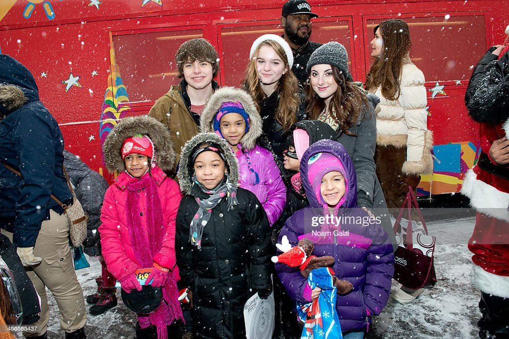 Brenden Meyer, Kerris Dorsey and Juliette Goglia pose with kids at the 2013 CitySightseeing New York holiday toy drive at PAL's Harlem Center on December 14, 2013 in New York City.