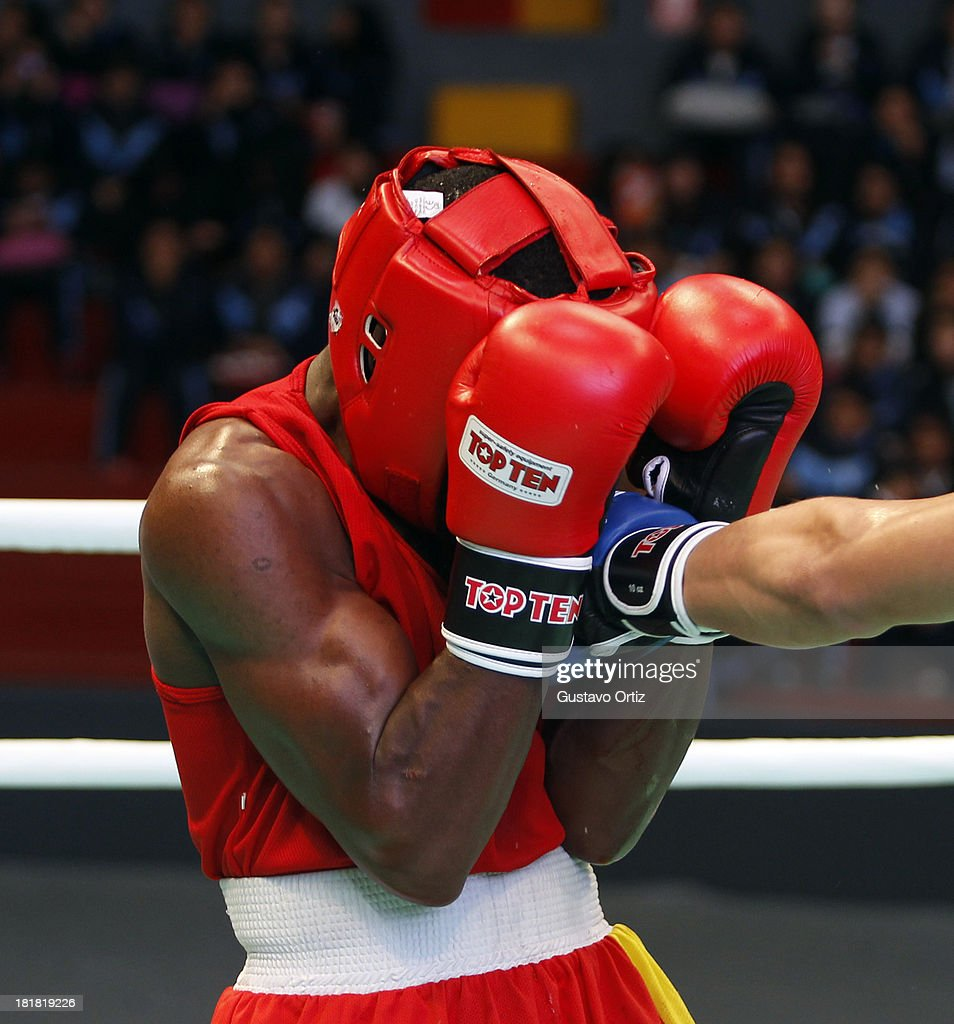 Brendo Coelho of Brazil fights (red) with Edwin Bennet of Venezuela (not in frame) during the Men's 64kg Boxing Finals as part of the I ODESUR South American Youth Games at Coliseo Miguel Grau on September 25, 2013 in Lima, Peru.