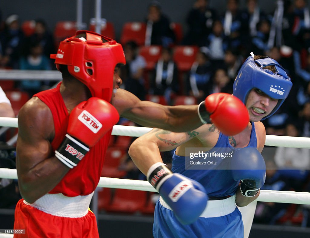 Brendo Coelho of Brazil fights (red) with Edwin Bennet of Venezuela (blue) during the Men's 64kg Boxing Finals as part of the I ODESUR South American Youth Games at Coliseo Miguel Grau on September 25, 2013 in Lima, Peru.