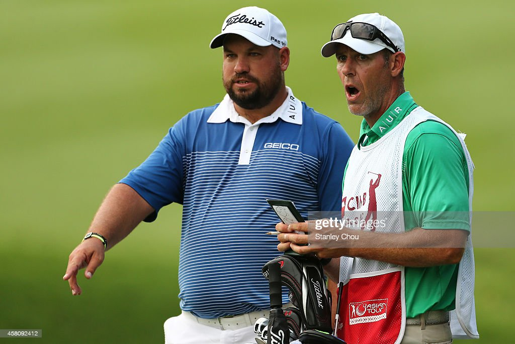 Brendon de Jonge of Zimbabwe waits with his caddie on the 5th hole during day one of the 2014 CIMB Classic at Kuala Lumpur Golf Country Club on...