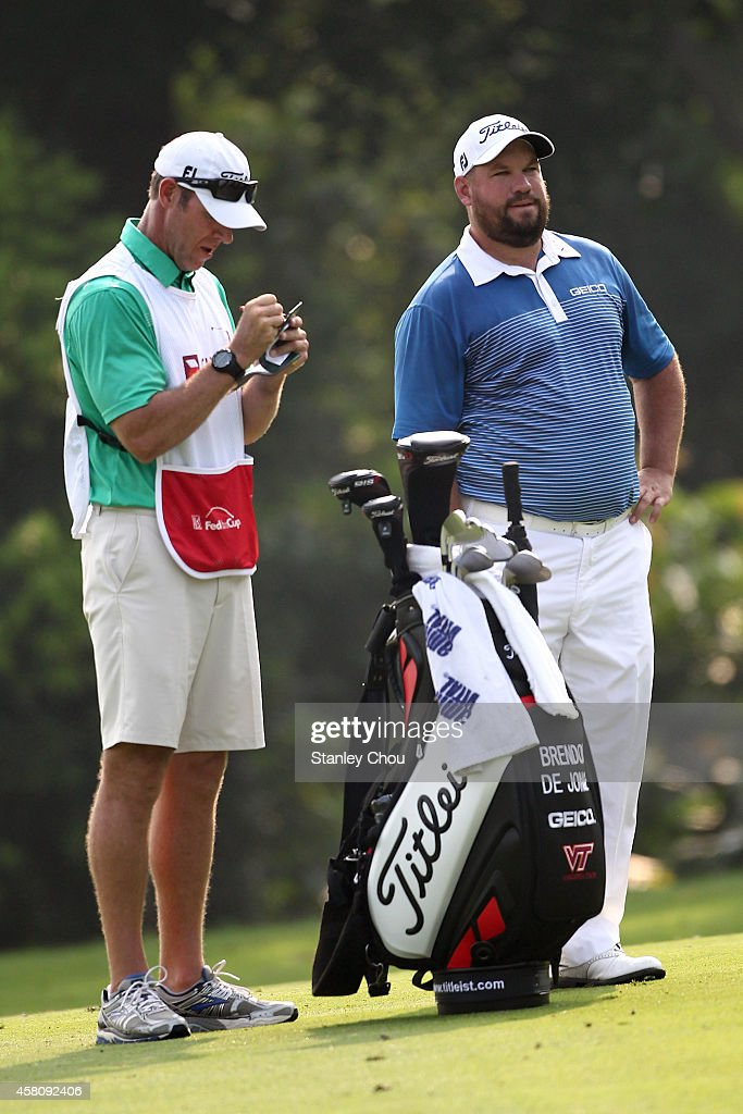 Brendon de Jonge of Zimbabwe waits with his caddie on the 7th hole during day one of the 2014 CIMB Classic at Kuala Lumpur Golf Country Club on...