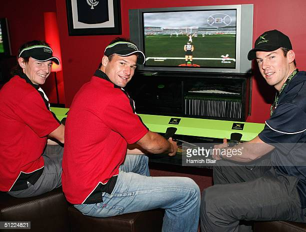 Brendon Goddard and Aaron Hamill of St Kilda take on Trent Sporn of Carlton at a computer game during the launch of the AFL Hall of Fame and...