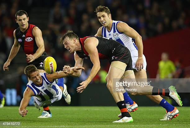 Brendon Goddard of the Bombers handballs whilst being tackled by Andrew Swallow of the Kangaroos during the round seven AFL match between the...