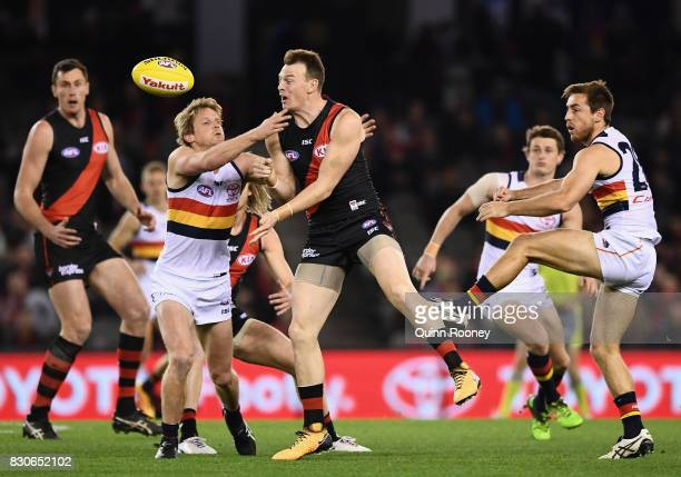 Brendon Goddard of the Bombers handballs whilst being tackled by Rory Sloane of the Crows during the round 21 AFL match between the Essendon Bombers...