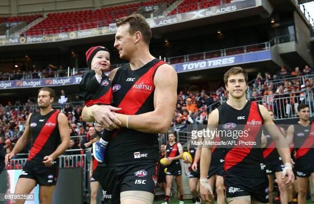 Brendon Goddard of the Bombers walks out onto the ground with his son for his 300th game before the the round 11 AFL match between the Greater...