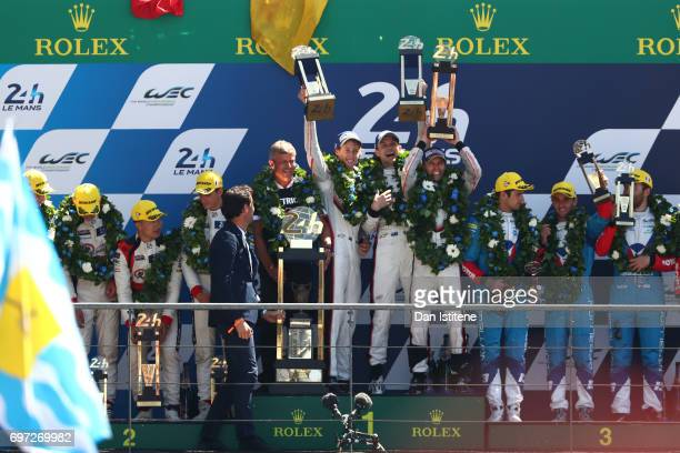 Brendon Hartley Earl Bamber and Timo Bernhard of the Porsche LMP Team lift their trophies as they celebrate on the podium with Vice President of...
