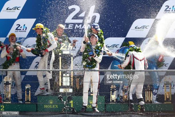 Brendon Hartley Earl Bamber and Timo Bernhard of the Porsche LMP Team celebrate on the podium with Vice President of Porsche's LMP1 Racing Program...