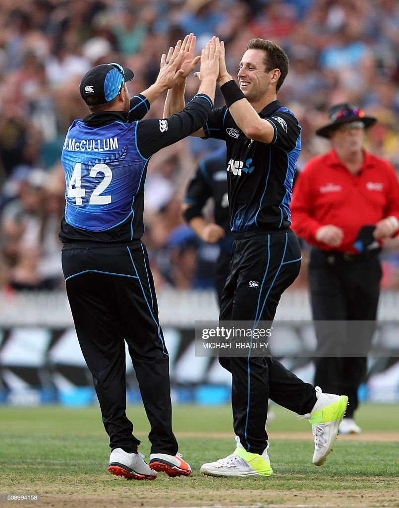 Brendon McCullum (L) and Matt Henry (R) of New Zealand celebrate after taking the wicket of Australia's David Warner during the third one-day international cricket match between New Zealand and Australia at Seddon Park in Hamilton on February 8, 2016. AFP PHOTO / MICHAEL BRADLEY / AFP / MICHAEL BRADLEY