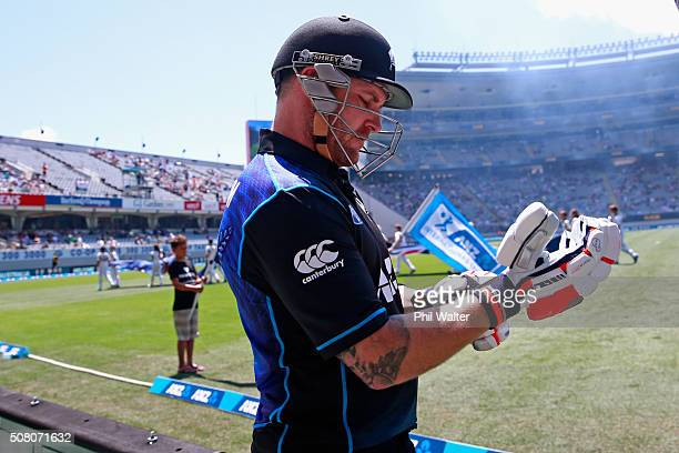 Brendon McCullum of New Zealand gloves up before taking the field in the One Day International match between New Zealand and Australia at Eden Park...