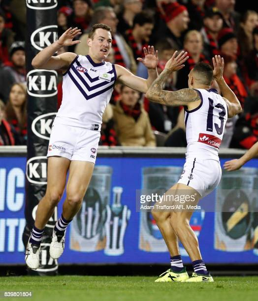 Brennan Cox of the Dockers celebrates a goal with Harley Bennell of the Dockers during the 2017 AFL round 23 match between the Essendon Bombers and...