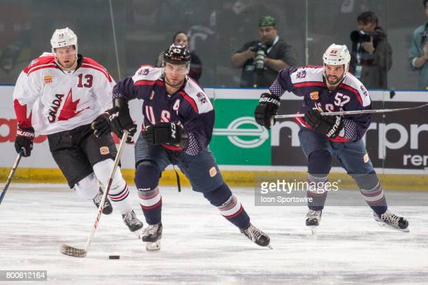 Brennan of Team USA controls the puck in front of Peter Holland of Team Canada and Brandon Bollig of Team USA during the Melbourne Game of the Ice...