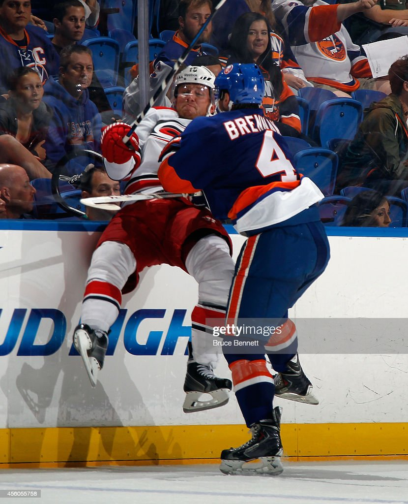 T.J. Brennan #4 of the New York Islanders hits <a gi-track='captionPersonalityLinkClicked' href=/galleries/search?phrase=Jiri+Tlusty&family=editorial&specificpeople=543236 ng-click='$event.stopPropagation()'>Jiri Tlusty</a> #19 of the Carolina Hurricanes into the boards during the third period at the Nassau Veterans Memorial Coliseum on September 24, 2014 in Uniondale, New York. The Hurricanes defeated the Islanders 4-2.