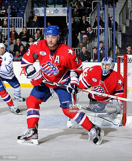 T J Brennan of the Rochester Americans keeps his eye on the puck in front of goalie David Leggio against the Toronto Marlies during AHL game action...